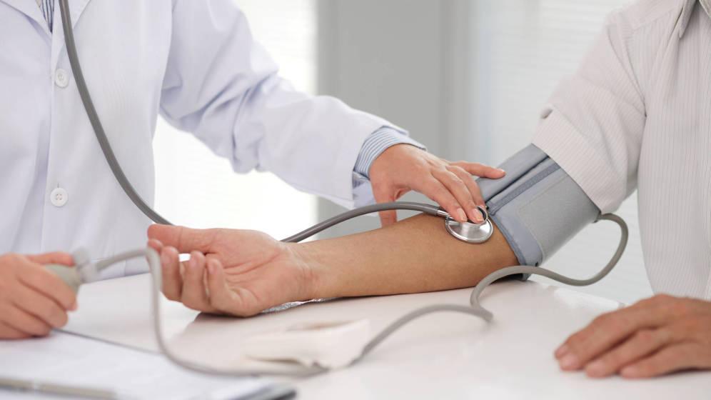 Un médico mide la tensión a un paciente para comprobar si tiene la presión arterial alta. (iStock)